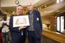 Wethouder Eric van der Burg laat de aangepaste ets zien met gouden sleutel, ons kado aan hem voor het openen van De Roze Poort. Op de achtergrond kijkt onze steun en toeverlaat Roble toe