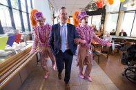 Geflankeerd door de Gebroeders Grimm komt Eric van der Burg, wethouder welzijn en zorg van de gemeente Amsterdam, de feestzaal binnen